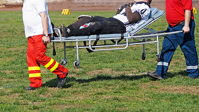 Photo of a american football player being carried off the field on a stretcher by two medics.