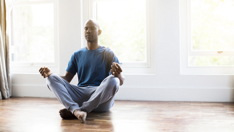 Photograph of man meditating in a studio