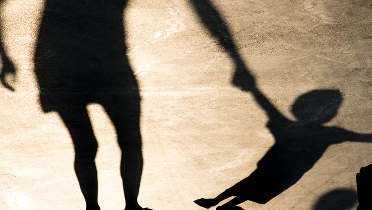 Shadows on the pavement of parent holding a child's hand