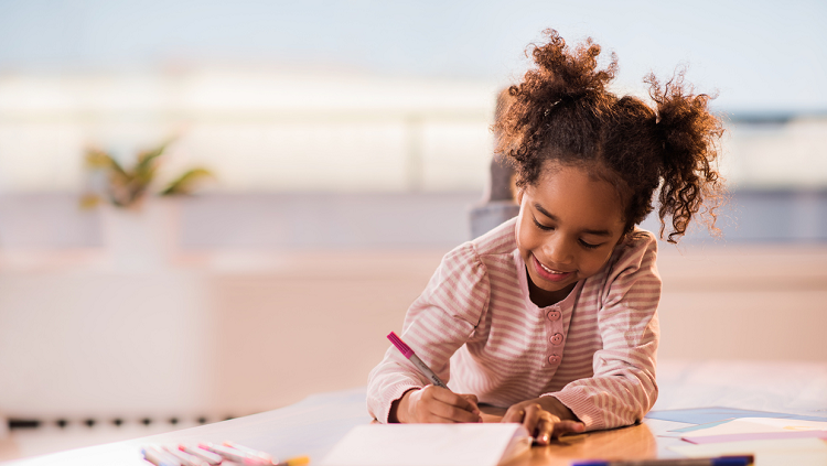 Photograph of a girl drawing happily