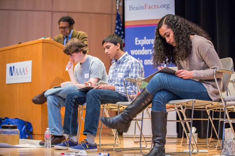 Three high school students compete in the final round of the DC Brain Bee while moderator Ben Walker looks on.