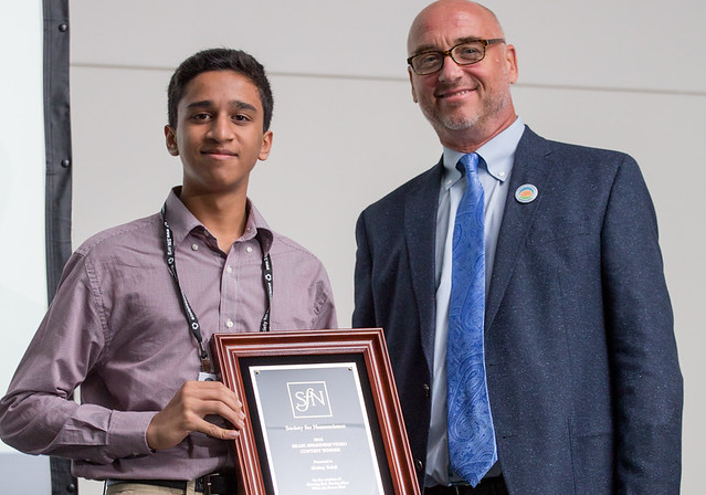 High school student Akshay Balaji, winner of the 2016 Brain Awareness Video Contest, receives his award at Neuroscience 2016 from Scott Thompson, chair of the Public Education and Communication Committee.