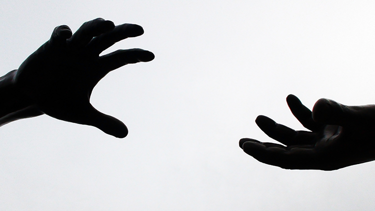 Hands separated reach out toward each other for help.