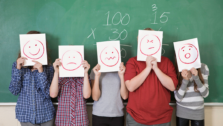 Image of children with drawn faces on paper in front of their faces