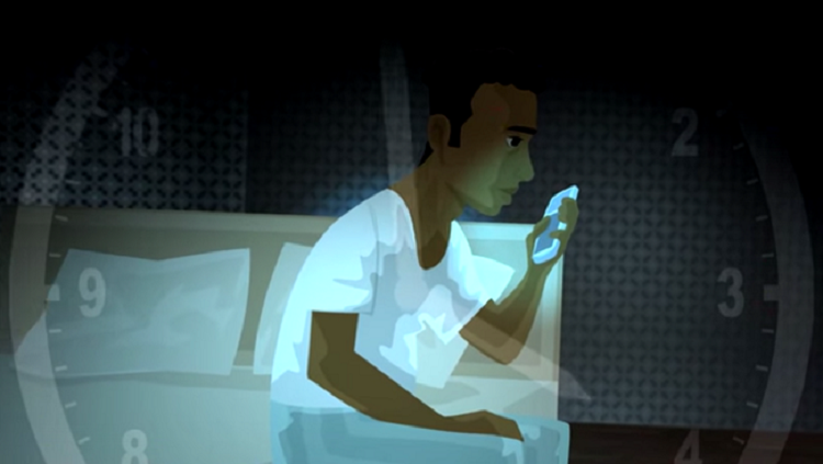 Image of a man on his bed looking at his phone