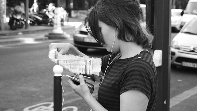 Woman looking at map and listening to music.
