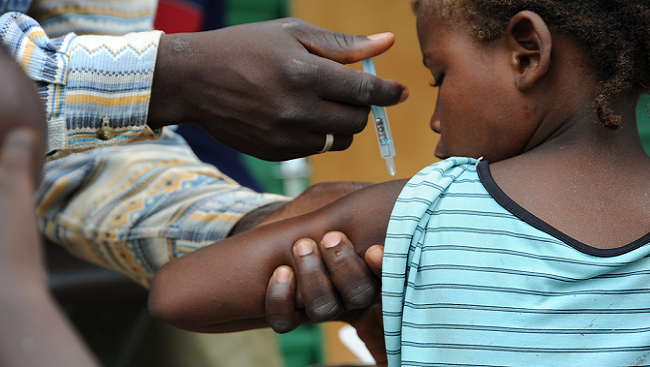 Child getting a vaccine. Photograph shows adult and holding the arm of a girl while she is getting vaccinated with a needle.