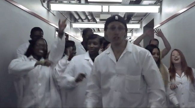 A man in a lab coat rapping.