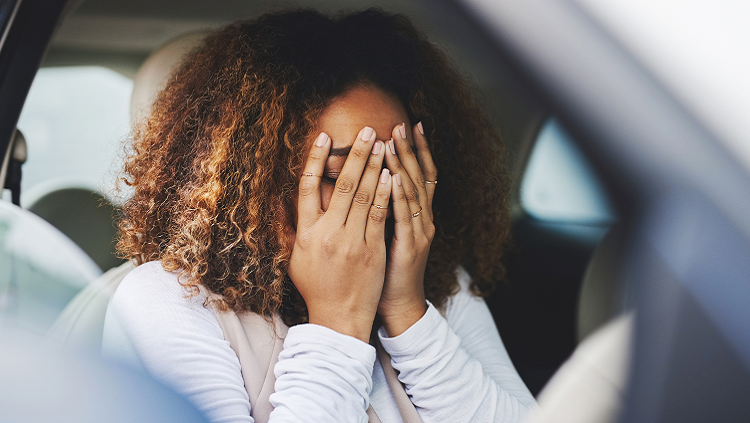 Photograph of woman looking distressed in her car