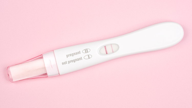 Image of a pregnancy test with pink background
