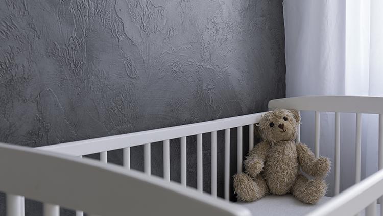 A teddy bear in a crib