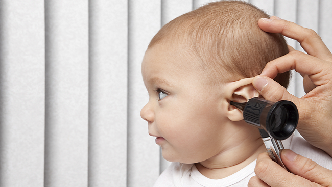 Baby with someone listening to its ear