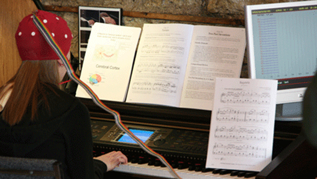 Girl with Electroencephalography Cap playing piano