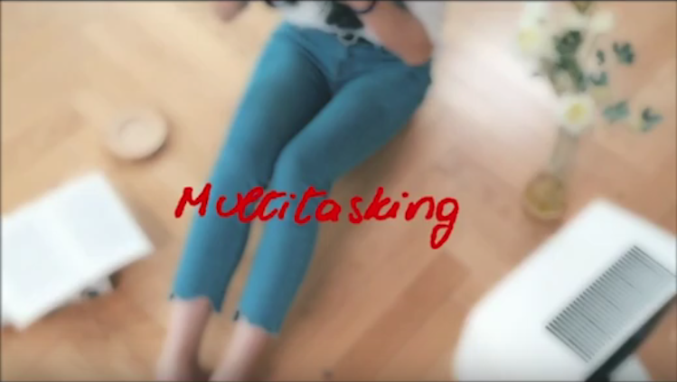 the word multitasking overlaying a blurry image of someone sitting on the floor