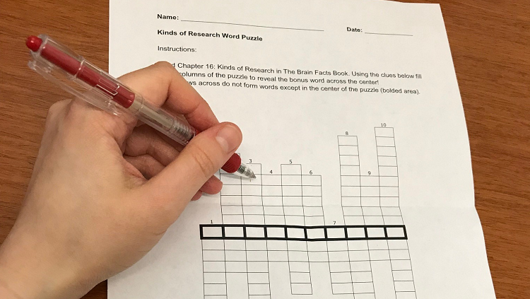 Photograph of a hand writing in a crossword puzzle