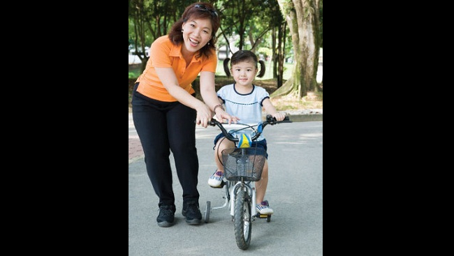 A woman helps her daughter ride a bike