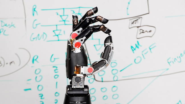Image of a neuroprosthetic hand in front of a white marker board with calculations written on it.