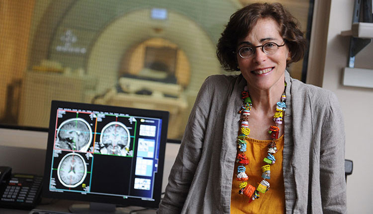 photo of marlene Behrmann next to computer with images of brains