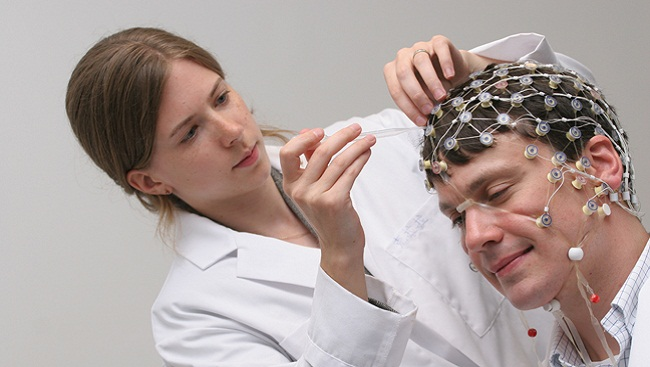 A researcher attaches electrotrodes to a man's scalp.