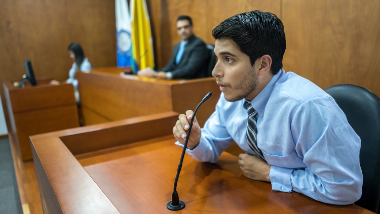 Man speaking on stand in a courtroom