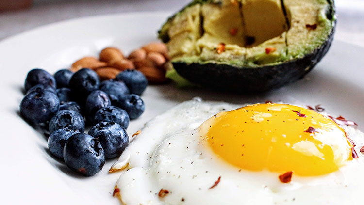 blueberries nuts eggs and avocado on a plate