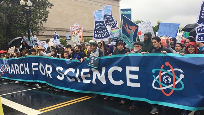 "Science supporters walk with ""March for Science"" banner down Constitution Avenue in Washington, D.C."