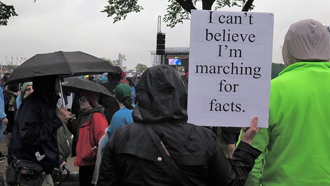 "Marcher stands with a sign that reads: ""I can't belive I'm marching for facts."""