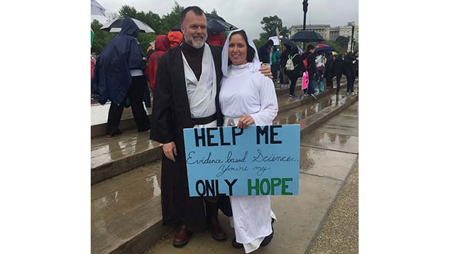 "Marchers dressed as Star Wars characters Luke Skywalker and Princess Leia with a sign that reads: ""Help me evidence based Science you're my only hope."""