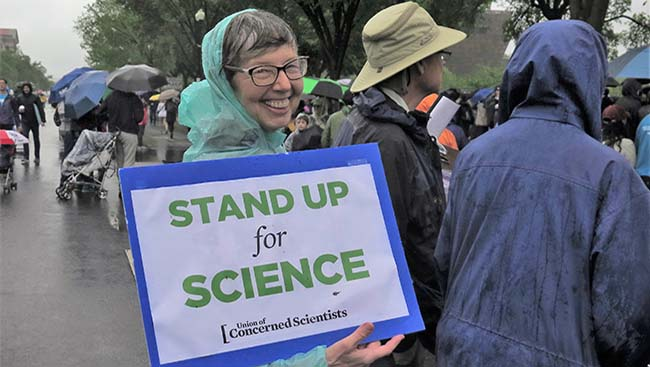 "March holds a sign from the Union of Concerned Scientists that reads: ""Stand Up for Science."""