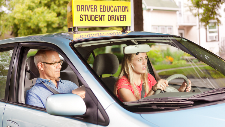 Photogprah of a scared teen driving with an adult is in the passenger's seat