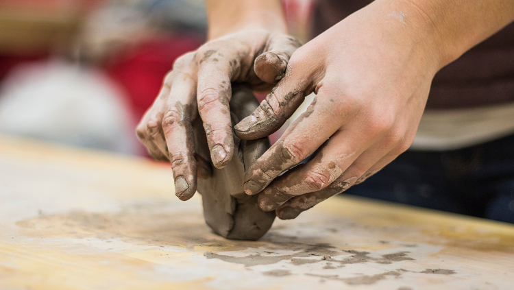 hands molding brown clay