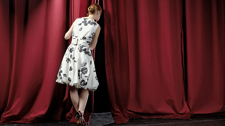 Photograph of woman peering out of red curtain
