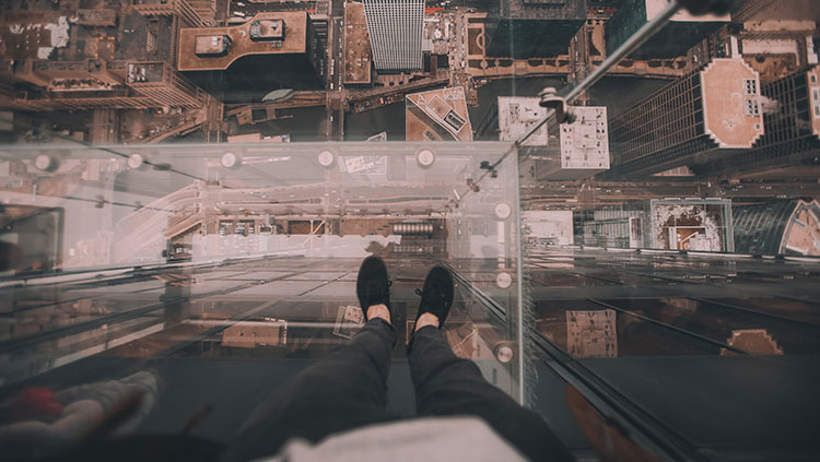 Person standing on glass platform over city