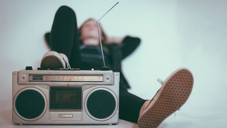 Young woman listening to a boom box while lying down