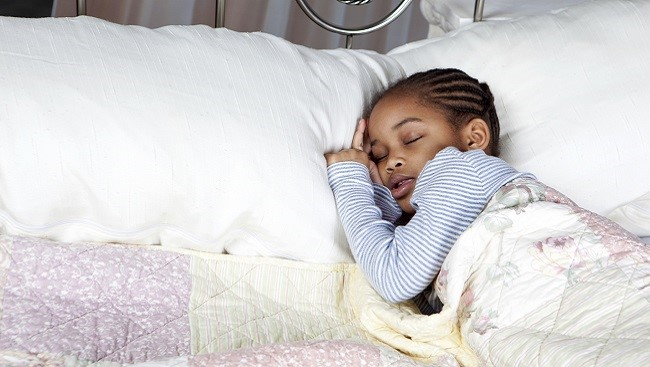 Photo of a girl sleeping in a bed, heading resting on a pillow.