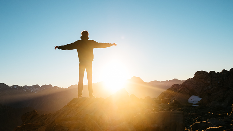 person with arms open watching the sun