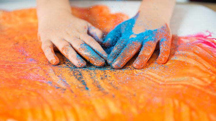 hands covered in blue glitter on orange paint