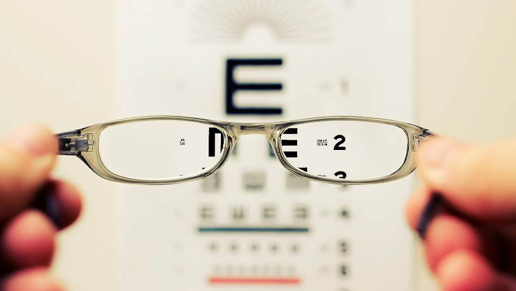 Person holding eyeglasses in front of an eye exam chart