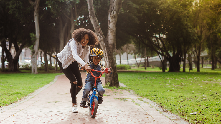 Toddler on a bicycle without training wheels and mom running along beside to steady the bike