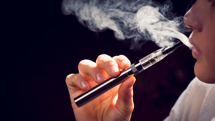 Photograph of a young person smoking an E-cigarette