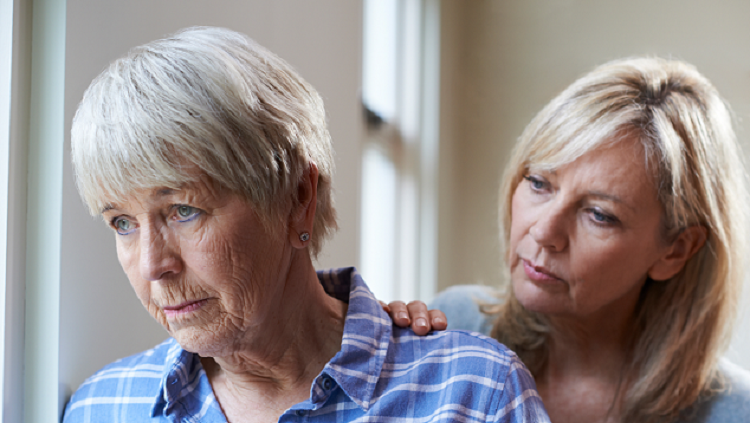 Image of elderly woman being comforted by younger adult
