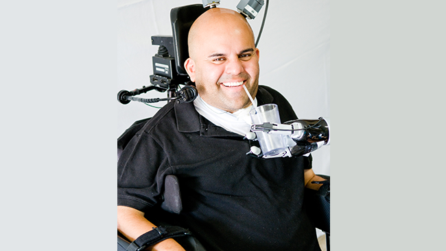 Photo of Erick Sorto drinking a glass of water assisted by a robotic arm that he controls with his thoughts.