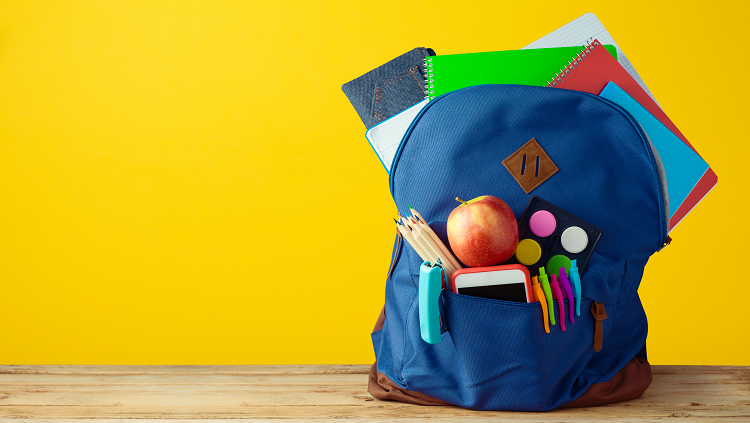 backpack with apple and notebooks yellow background