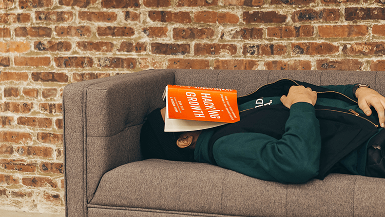 man asleep with a book on his face
